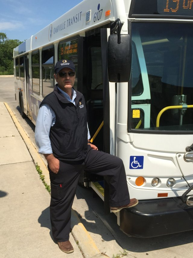 Bus Driver with foot on front bumper of Oakville Transit Bus