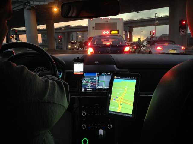 Uber Driver looking from the back seat of a car driven by and UBER Driver