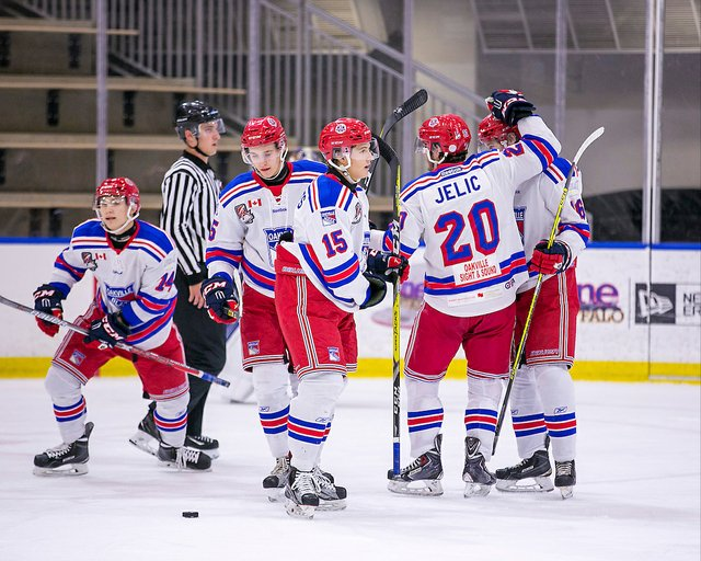 Matt Hayami #14 of the Oakville Blades scores on a power play goal. Assists by Evan Brown #16 and Daniel Jelic #20 of the Oakville Blades