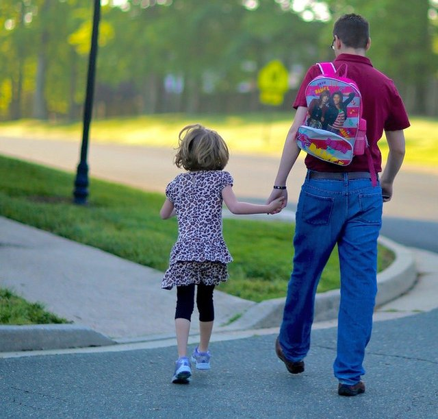 Father walking with young daughter, He is carrying her backpack