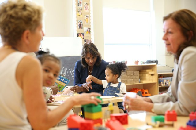 Indira Naidoo-Harris working with a child in a class