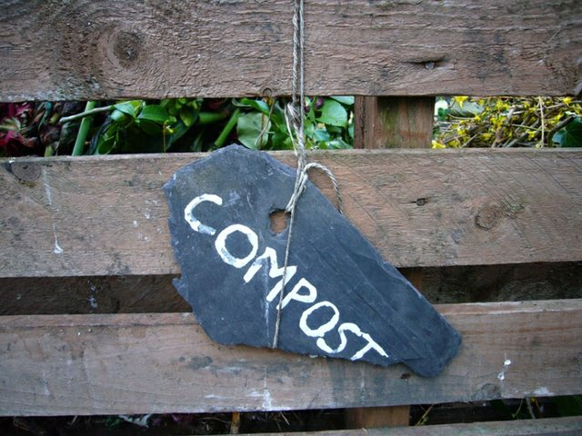 rock on bench that says compost