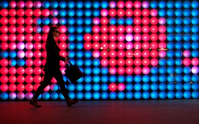 lady with briefcase in front of light display