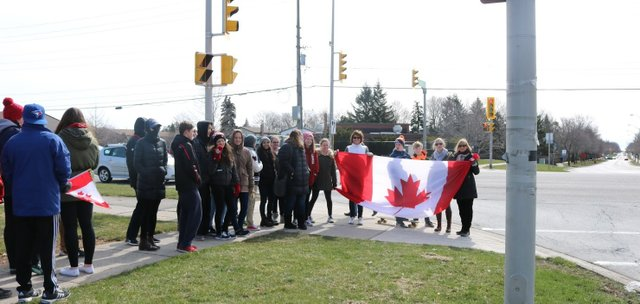 Students walking with Canadian Flag