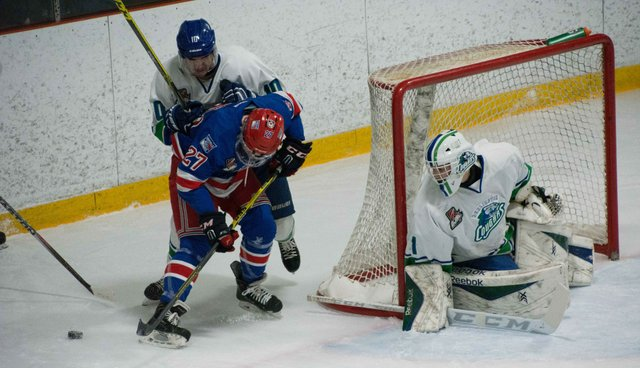 Three Hockey Players around the net