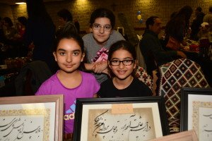 two girls and one boy holding plaques