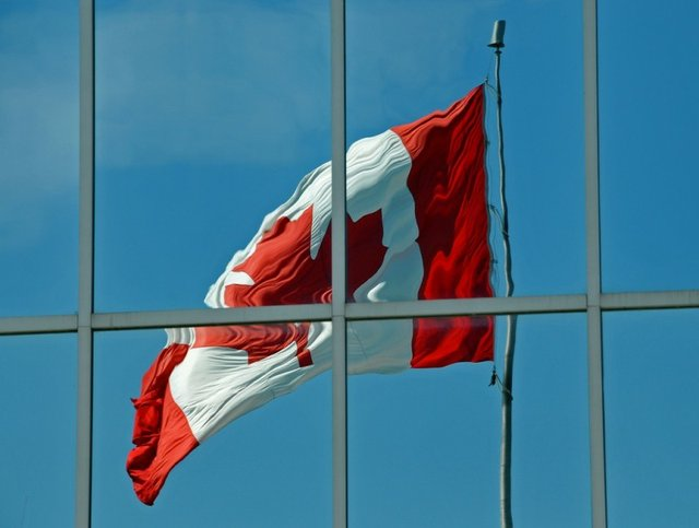 Canadian Flag waving reflected off mirrored building