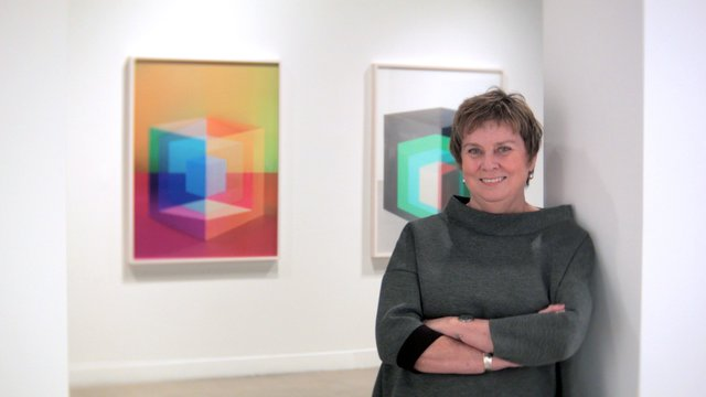 Marnie Fleming with short hair in a sweater in art gallery