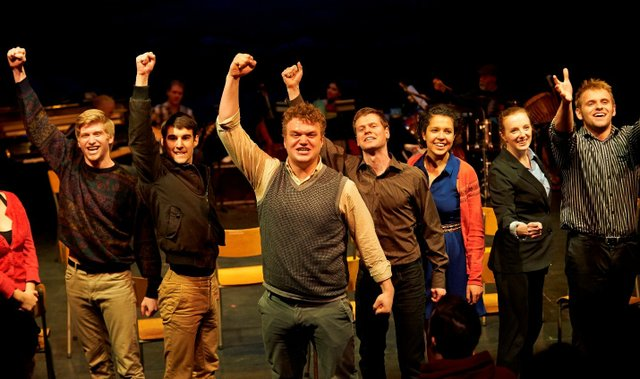 Theatre students dressed casually with right arms raised with fists