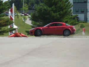 red sports car by fallen traffic cones