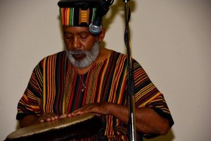 Black Male in traditional garb with white beard playing drums