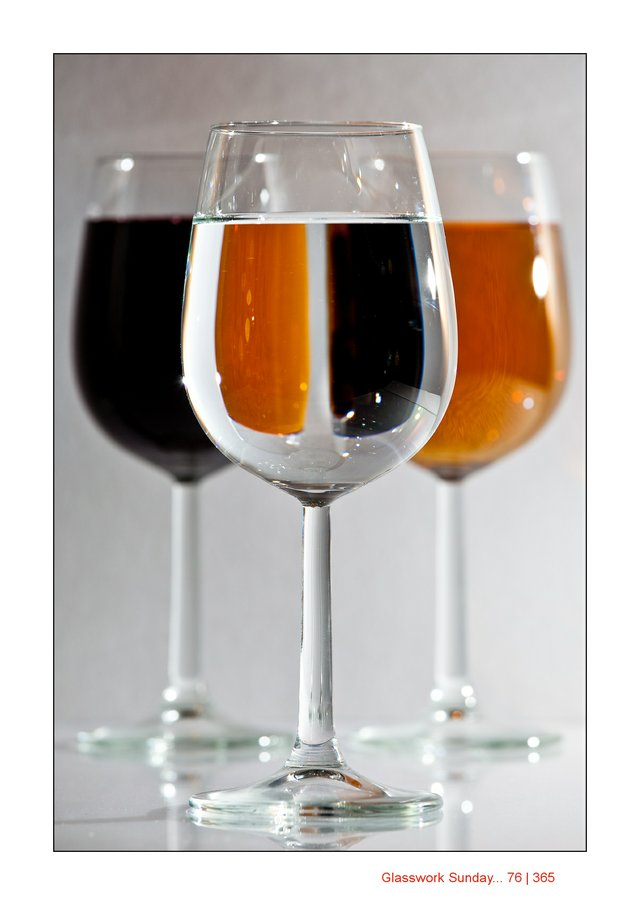 Three wine stem glasses, red, amber and clear water