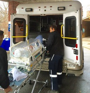 Baby in incubator being loaded into an ambulance