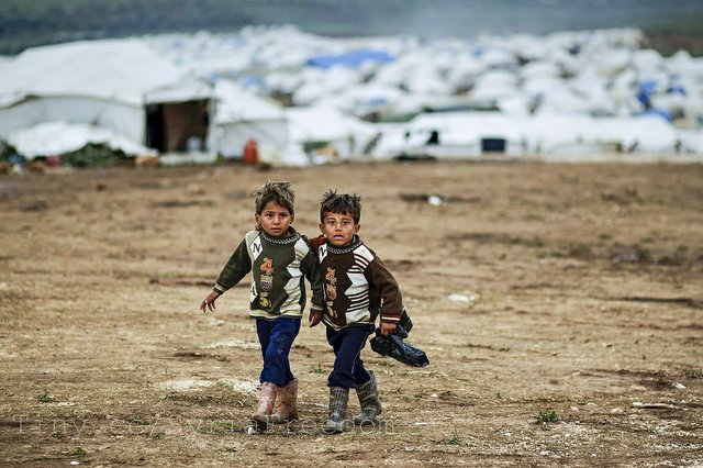 Syrian boys, whose family fled their home in Idlib, walk to their tent, at a camp for displaced Syrians, in the village of Atmeh, Syria,