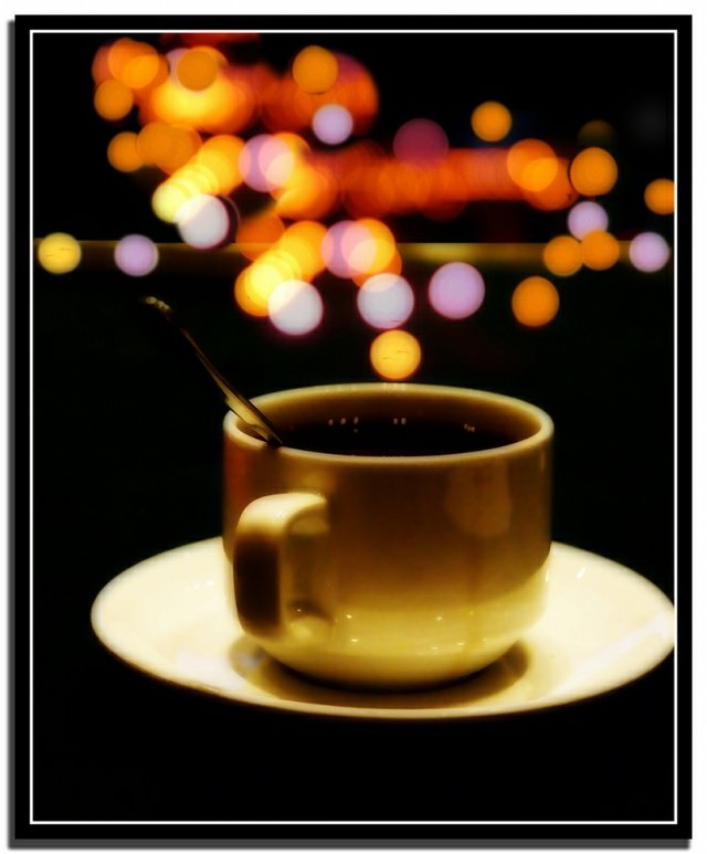 cup of coffee with colour lights in the background