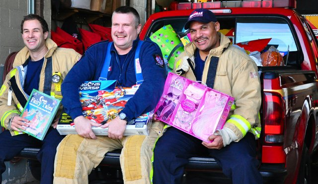 Firefighers holding unwrapped gifts