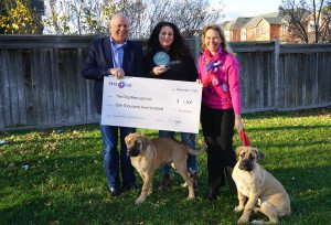 Three people 2 dogs with presentation cheque