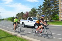 two cyclists on bike lane beside town truck