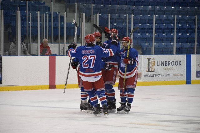 Oakville Blade players on the ice celebrating a goal