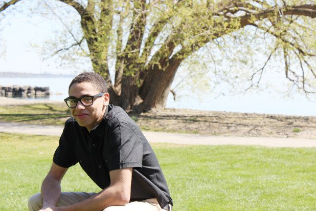 young black male with glasses in a park