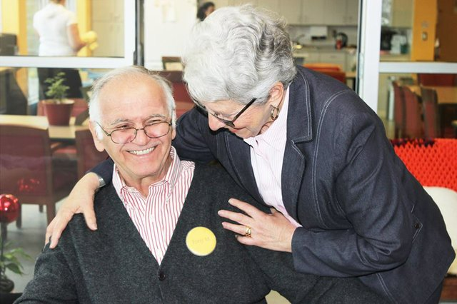 Elderly couple indoors with wife hugging husband who is sitting down