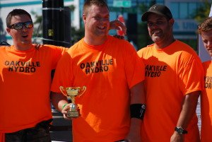 Three men in Orange T's with small trophy