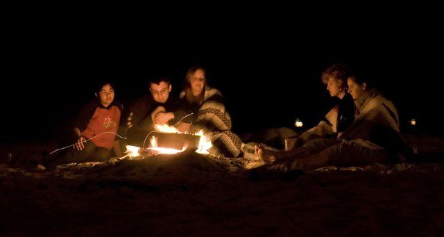 Group of children and teenagers around a bond fire at night