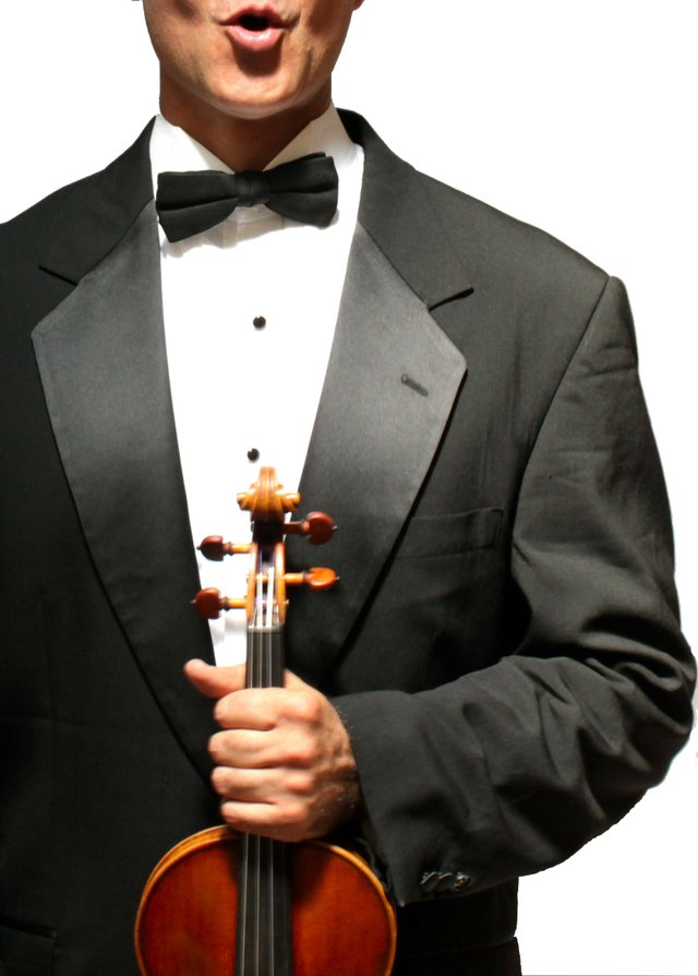 man in tuxedo holding a violin