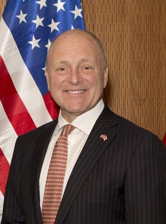 Older balding man in suit in front of the US Flag