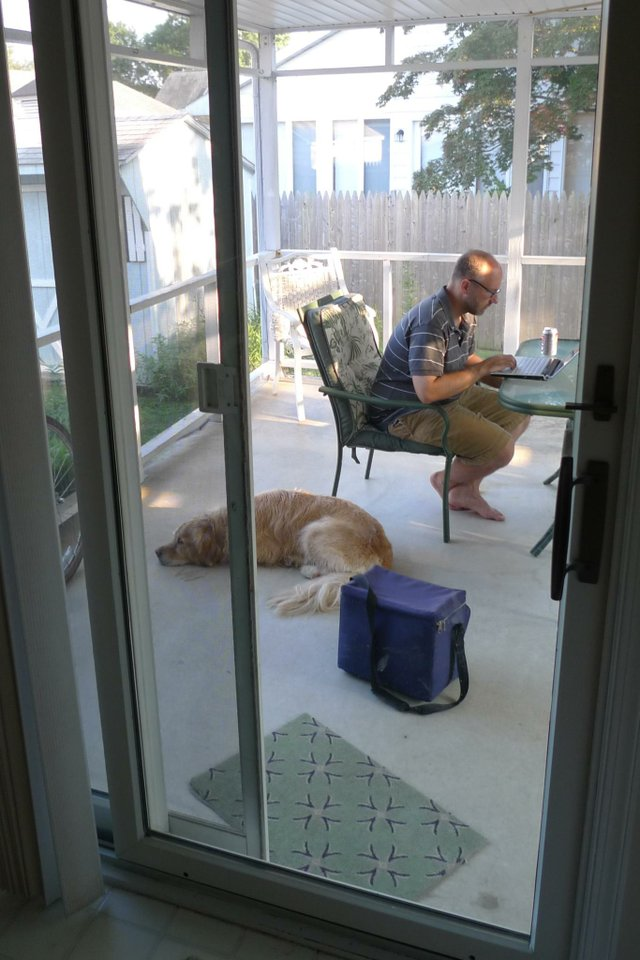 Man working on a computer on the porch with dog at his feet