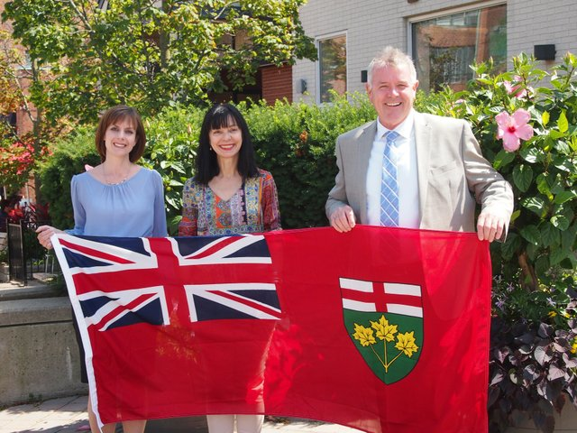 Two women and a man hold up the Ontario Provincial Flag
