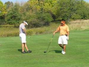 Two men in shorts playing golf