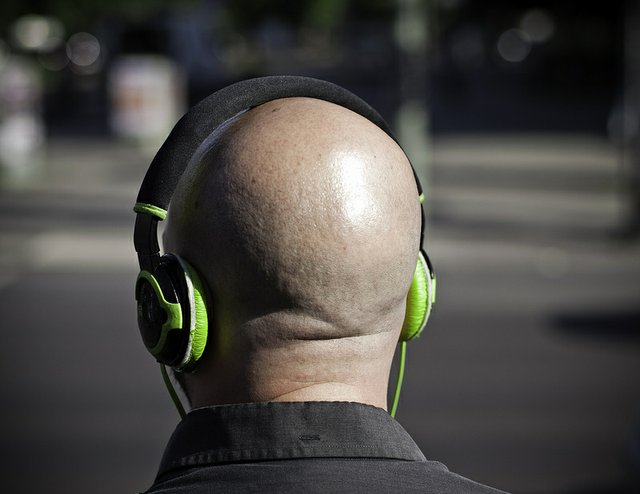 back of bald head with green headphones on