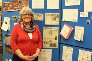 Mary (Ceelen) Liefers, former staff member photographed next to her picture in the newspaper for St. Michael School`s 25th Anniversary.