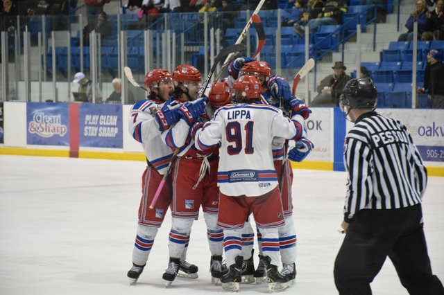 Oakville Blades in congratulatory hug on the Ice