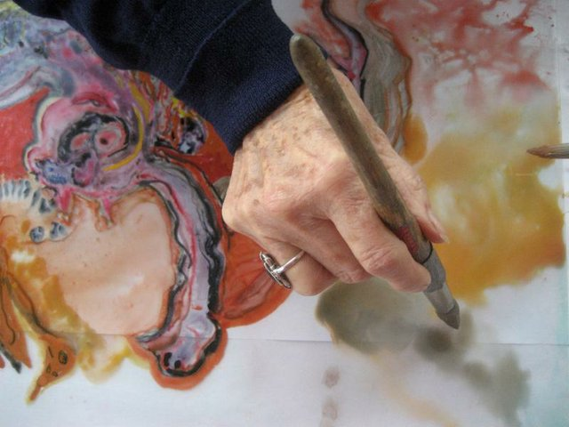 Elderly Hand holding a paint brush over an unfinished work of art