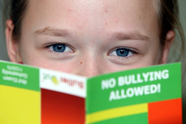 Child reading a anti-bullying brochure