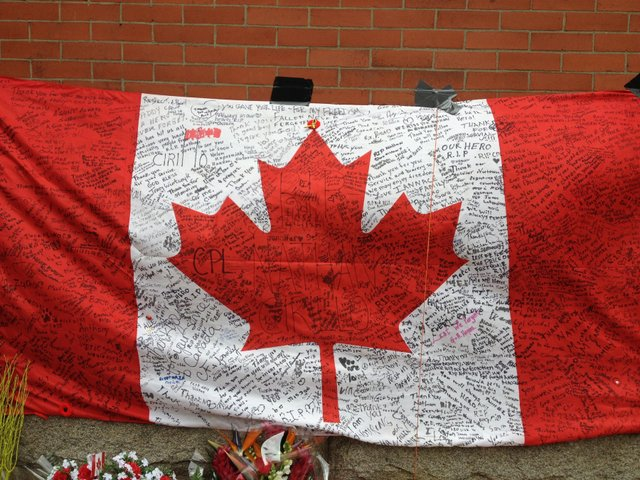Cdn flag on armoury wall in hamilton with tributes