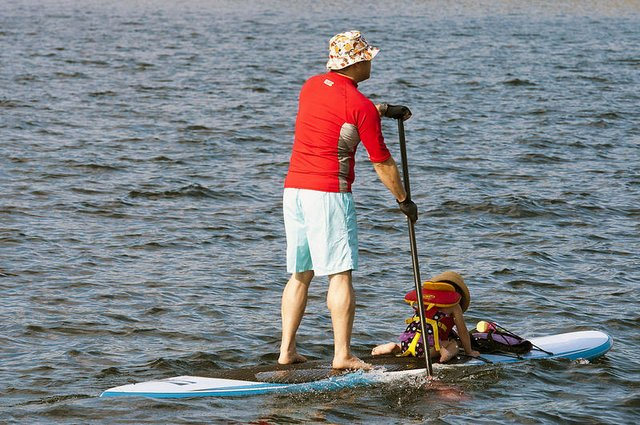 Man paddle boarding with his baby daughter