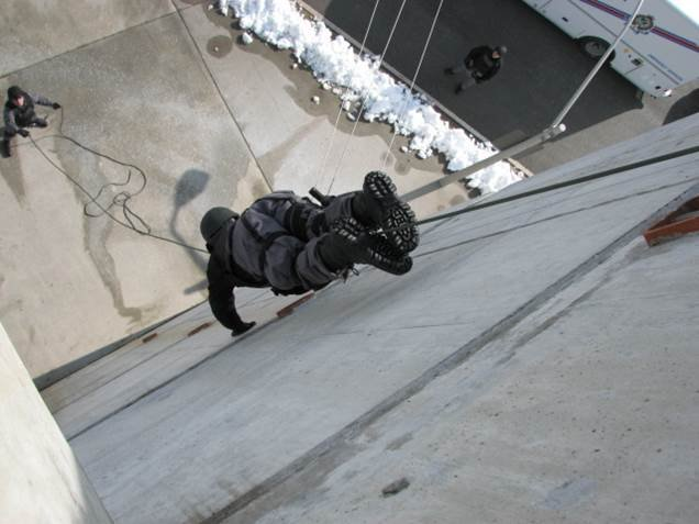 Police person repelling down a building