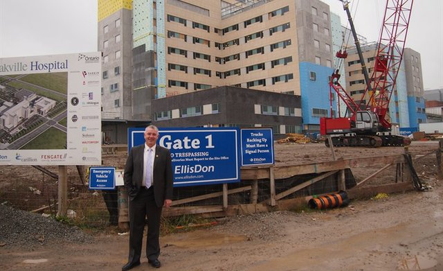 Standing in front of Gate 1 of the New Oakville Hospital, Oakville News, Kevin Flynn, MPP, Minister of Labour, Ontario Government