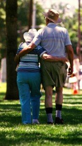 Elderly couple with there arms around each other walking in a park