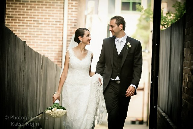 Wedding couple formally dressed alone walking down a small alley way to a backyard