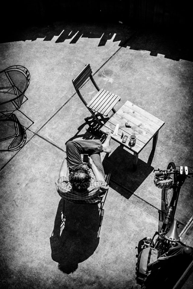 B/W top view of man on patio reading