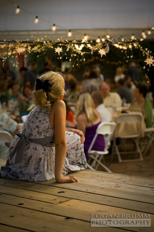 Young girl over looking an evening party outside