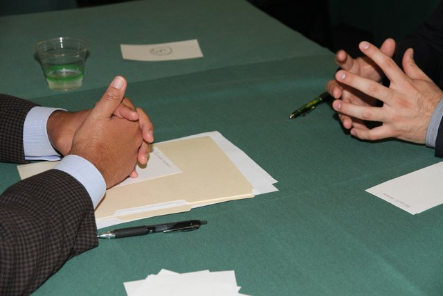 two set of hands on a table facing each other going through an interview