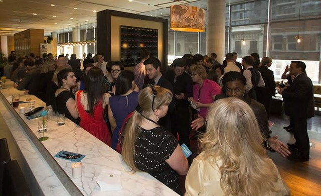 Invited students, alumni, staff, and family enjoying a drink at the TIFF Lightbox