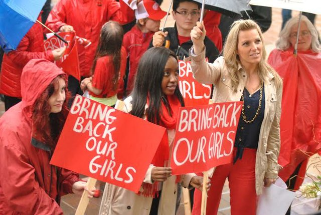 Young ladies in the rain wearing read in #BringourGirlsBack