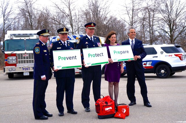Chiefs of Police, Fire, Paramedics, Halton plus Regional Chair Gary Carr in front of Fire Truck, Police Car, Ambulance,